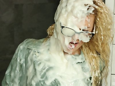 Glamorous nerdy blonde covered with cream from a fake glory hole cock